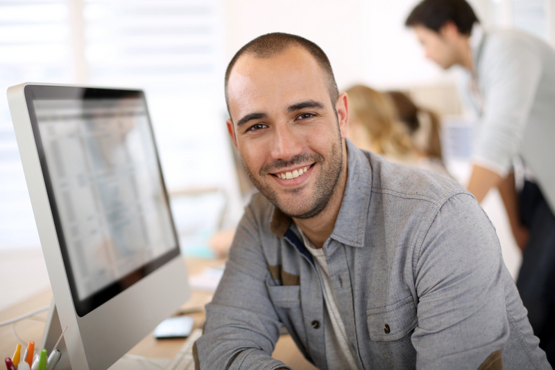 bigstock-Cheerful-guy-sitting-in-front--53542399